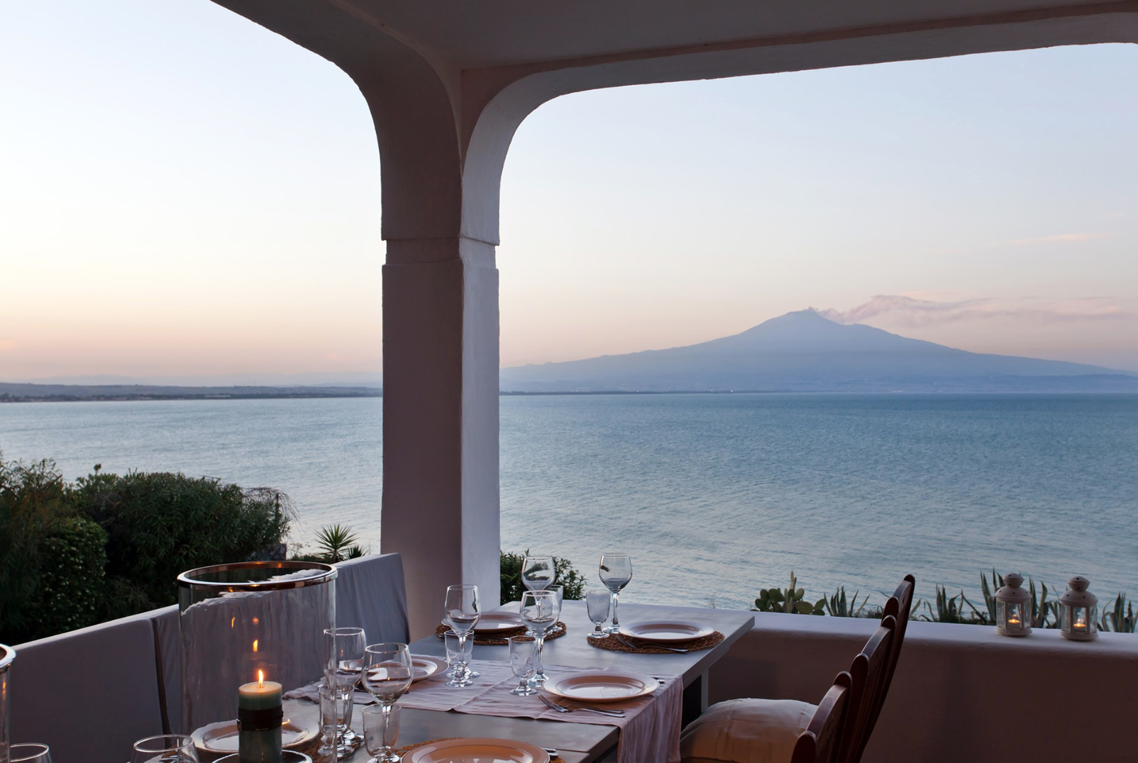 al fresco dinner with sunset view behind Mount Etna